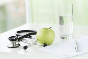 Healthy lifestyle items: green apple, glass of water, stethoscope and blank notebook on the table.