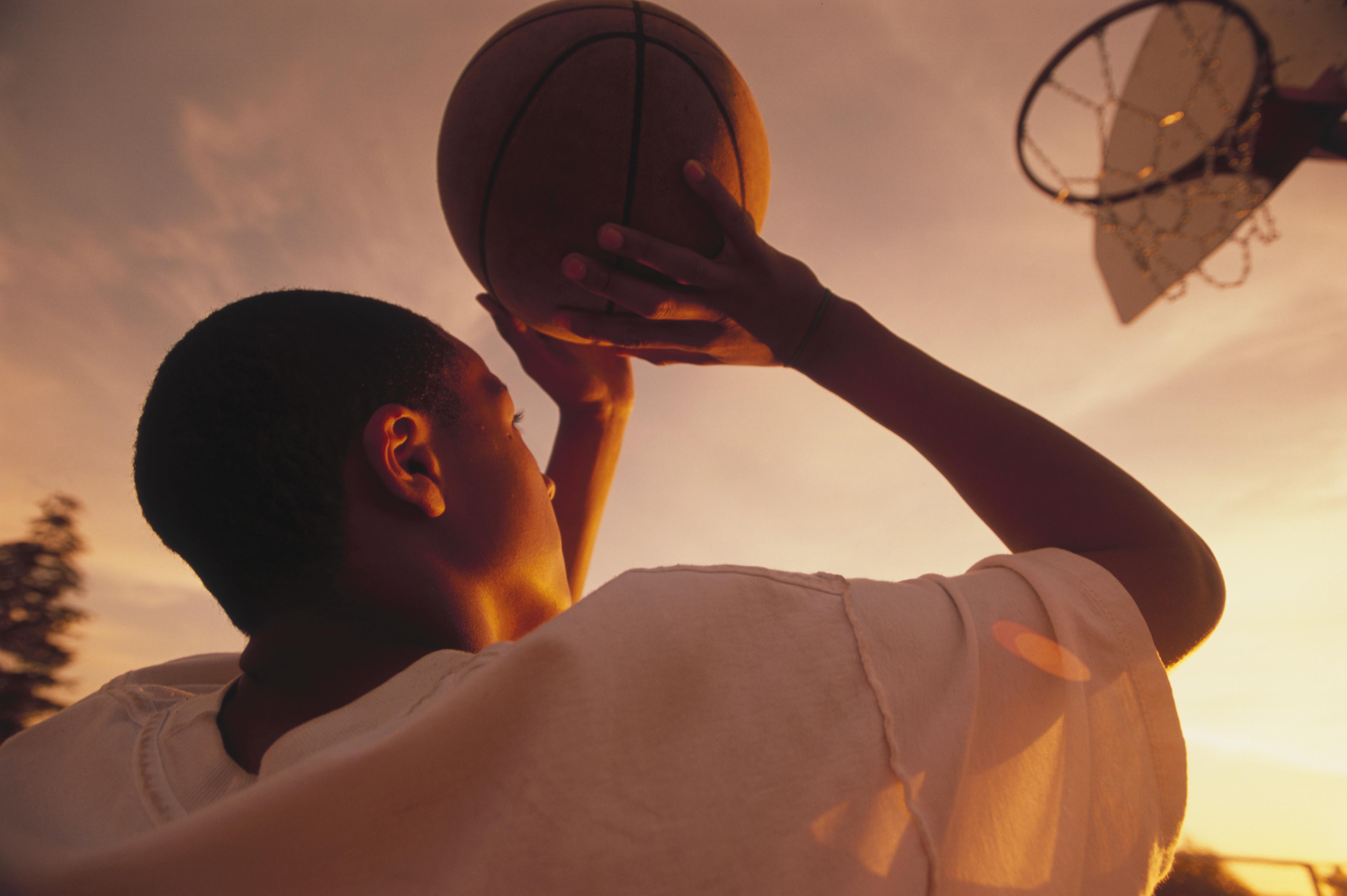 Boy Aiming Basketball at Hoop