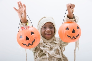 Black boy in mummy costume holding jack o'lanterns