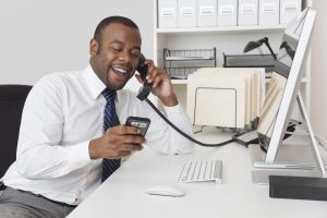Black businessman using two telephones at one time